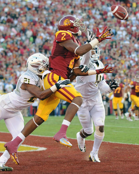 USC receiver Robert Woods catches a touchdown pass in front of Oregon defenders Avery Patterson, left, and Erick Dargan in the second quarter Saturday at the Coliseum.