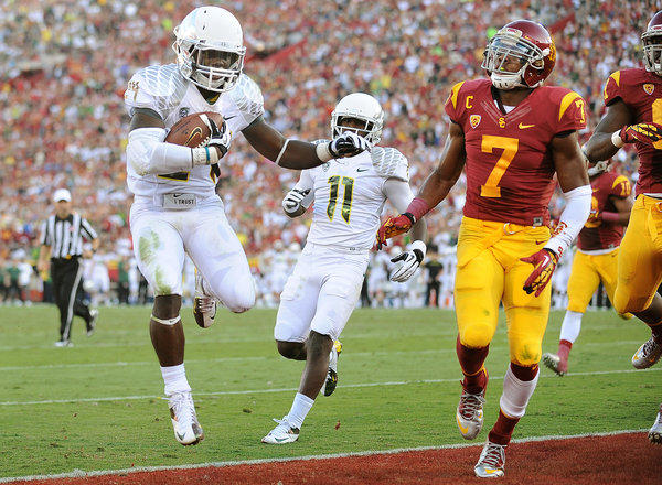 Ducks running back Kenjon Barner, who scored five touchdowns, beats Trojans safety T.J. McDonald to the end zone in the second quarter Saturday.