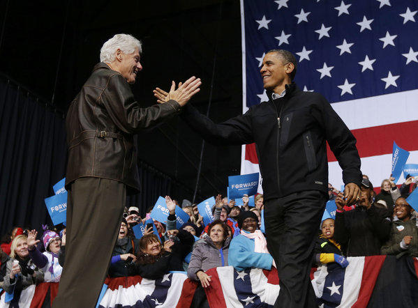 Former President Bill Clinton greets President Obama at a late-night campaign rally in Bristow, Va.