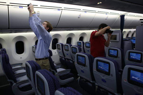 Some inaugural passengers take photos before United Airlines flies its first flight from Houston to Chicago in its new Boeing 787 Dreamliner aircraft Sunday. The aircraft has a host of passenger amenities, such as larger windows, special lighting and filtered air.