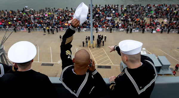 Petty Officer First Class John Williams waves his hat at family members gathered on the pier for the return of the USS Enterprise Sunday in Norfolk.