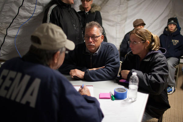 Residents of Staten Island speak with a FEMA representative, left, on Nov. 3 in Midland Beach after Superstorm Sandy left millions without power or water in the Staten Island borough of New York.