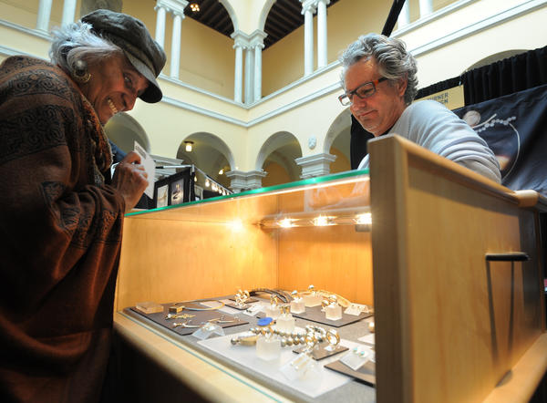 Phyllis Anderson from Glen Burnie, looks at jewelry made by Thomas Turner, pictured at right, at the Jewelry Fair at the Walters Art Museum on Sunday.  The fair included about 17 artists from several states.