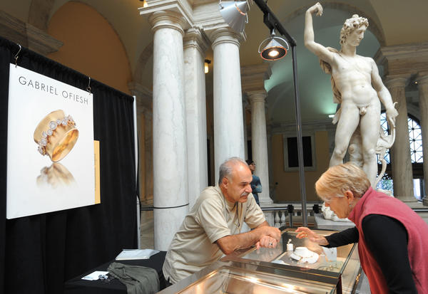 Jewelry artist Gabriel Ofiesh from Charlottesville, Va., shows his jewelry to Denise Brown from Annapolis under the statue of Apollo by Pietro Francavilla.