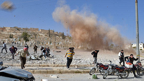 Syrians flee as a second bomb explodes while civilians were attempting a rescue at a bombed building in Al Bab in Aleppo province.