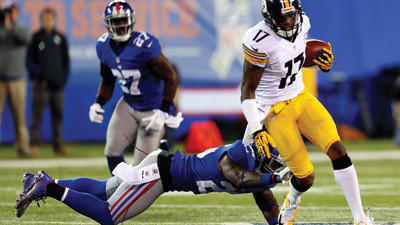 Pittsburgh Steelers wide receiver Mike Wallace breaks a tackle for a touchdown during the second half against the New York Giants on Sunday in East Rutherford, N.J.