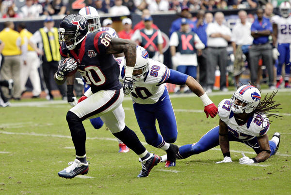Andre Johnson #80 of the Houston Texans breaks the tackle of Leodis McKelvin #21 of the Buffalo Bills and Nick Barnett #50 of the Buffalo Bills at Reliant Stadium on November 4, 2012 in Houston, Texas. Houston defeated Buffalo 21-9.