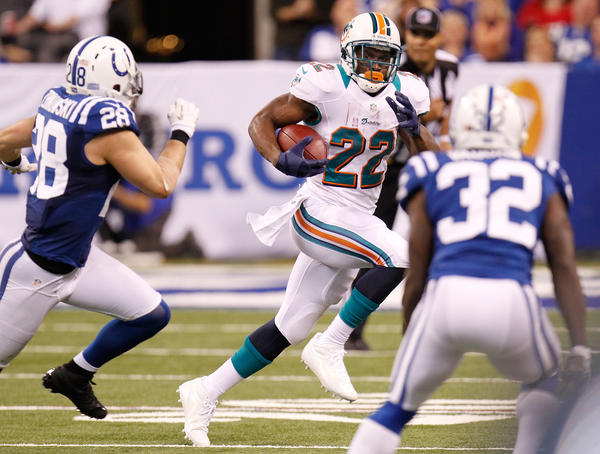 Reggie Bush #22 of the Miami Dolphins looks for running room between Tom Zbikowski #28 and Cassius Vaughn #32 of the Indianapolis Colts during a fourth quarter run at Lucas Oil Stadium on November 4, 2012 in Indianapolis, Indiana. Indianapolis won 23–20.