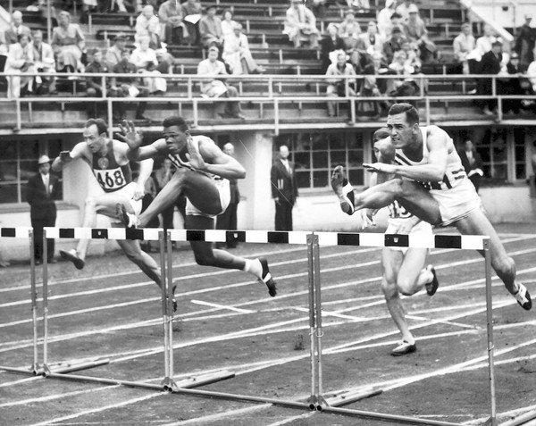 This 1952 file photo shows Milt Campbell, center, getting set to clear the final hurdle to make him the winner in the fifth heat of the 110-meter hurdles event in the Olympic decathlon at the Helsinki Games. He won a silver medal in the event, finishing second to Bob Mathias. Four years later, at the Melbourne Summer Games, he won a gold medal.