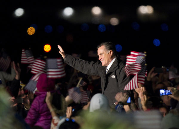 Mitt Romney waves to the crowd after his arrival at Smithfield Foods flight center hanger Sunday night at Newport News Williamsburg International Airport.