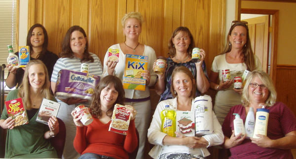 Women's Resource Center domestic abuse program staff hold items being collected during the Harvest Food and Supply Drive: (front, from left) Jen Rashleigh-Houser, Angie Linsenman, Nicole Bruskotter, Kim McQuistion; (back) Stacey Ettawageshik, Jennifer DeVries, Amy Strohpaul, Monica Webb and Jamie Winters.