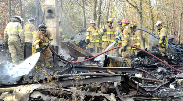 Firefighters hose down the charred remains of a mobile home at 1807 Back Road that was destroyed in a fire Monday morning. One person was found dead in the mobile home.