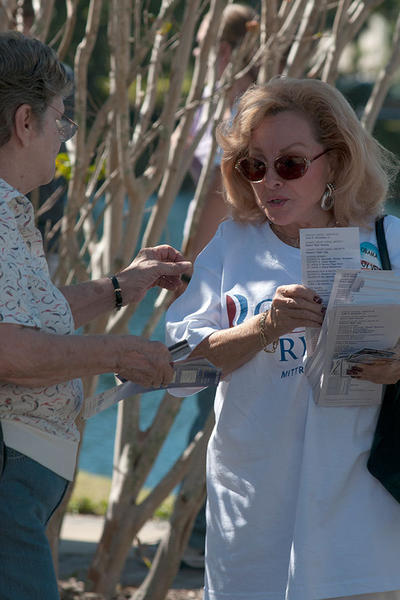 Lucille Justin hands out a voting guide to a voter in the parking lot before voting. Hundreds lined up in a line that weaved it's way around West Regional Library in Plantation as early voting in Broward county comes to a close. Average wait time was a little over 2 hours.