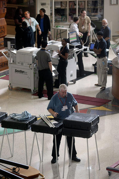 Klaus Macon helps set up voting equipment for early voting at the African-American Research Library and Cultural Center.