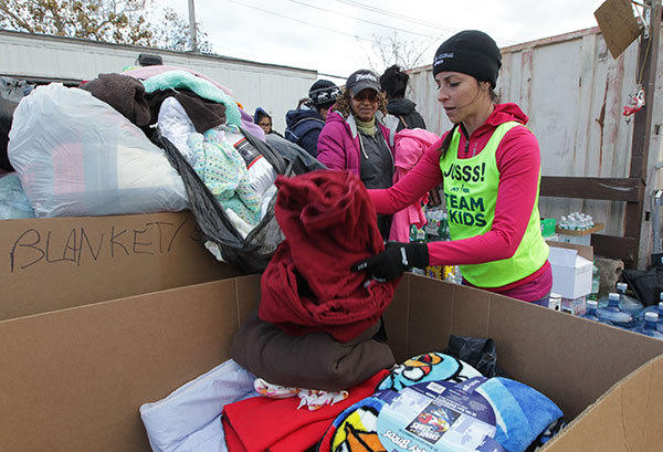 Runner Joselyn Fine, 34, who would have run the ING New York City Marathon, spends the afternoon volunteering by unloading and organizing emergency supplies near Midland Beach as New York recovers from Hurricane Sandy on November 4, 2012 in Staten Island, New York.