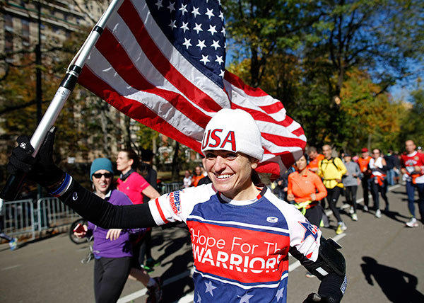 A runner with an American flag participates in a fun run in Central Park after the New York Road Runners cancelled the 2012 New York Marathon due to the impact of Hurricane Sandy hitting the region, New York, November 4, 2012.