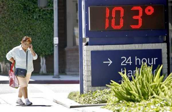 A pedestrian walks by a temperature sign on Central Ave. in Glendale.