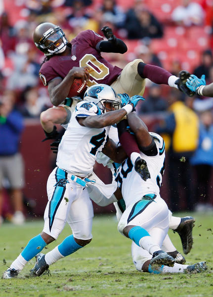 Quarterback Robert Griffin III #10 of the Washington Redskins is tackled by Captain Munnerlyn #41 and James Anderson #50 of the Carolina Panthers during the fourth quarter of the Panthers 21-13 win at FedExField on November 4, 2012 in Landover, Maryland.