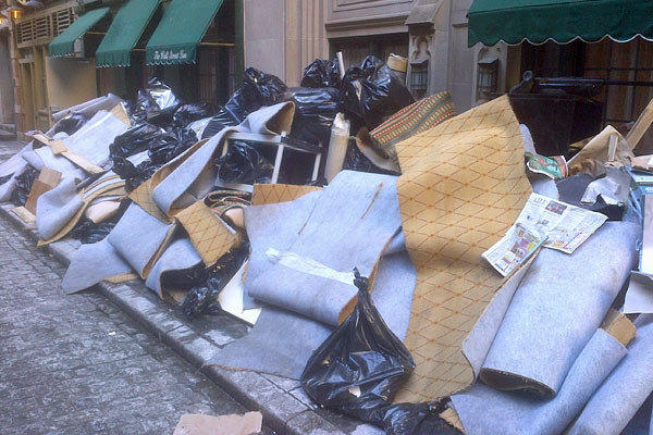 Carpeting and debris pile up on the curb in New York City's financial district as crews work to repair damage caused by super storm Sandy.