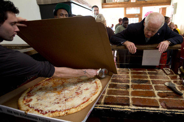 Vice President Joe Biden watches as a Benny Marconi's employees cuts a pizza in Roanoke, Va.