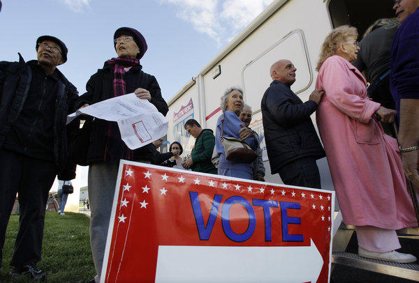 Voters stand together in Burlington, N.J., outside a Mobile Voting Precinct, as they inquire about voting. Many victims displaced by Superstorm Sandy took advantage of offers to vote early.