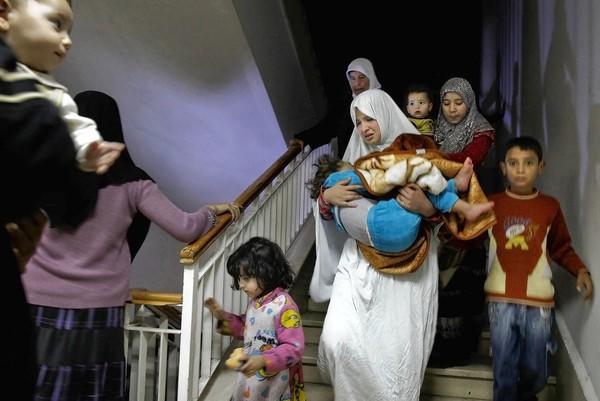 "Syrian women and children run to the basement of a building housing several rebel fighters during an attack last week by government tanks and helicopters in Aleppo. ""We gave the regime an excuse to attack civilians,"" one rebel leader said of the fighters' presence in the city."