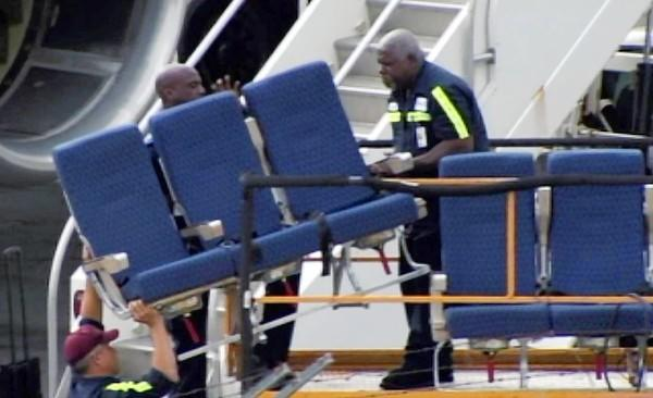 Seats from an American Airlines 757 are carried off last month at Logan International Airport in Boston.