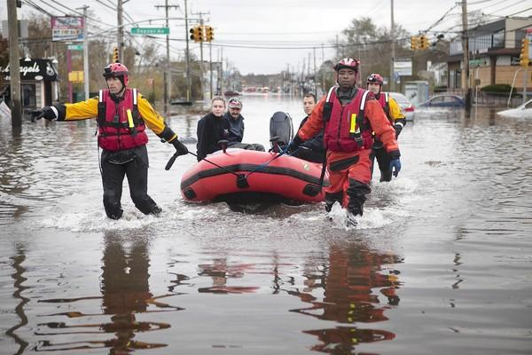 After superstorm Sandy, New York firefighters help residents make their way to higher ground last week in Staten Island.
