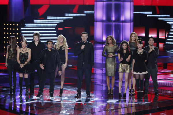 Teams Blake and Adam compete on 'The Voice': (l-r) Cassadee Pope, Michaela Paige, Terry McDermott, Julio Cesar, Liz Davis, host Carson Daly, Amanda Brown, Joselyn Rivera, Loren Allred, Melanie Martinez, Bryan Keith