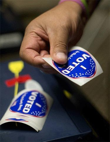 An election worker prepares voting stickers to hand out to voters in Las Vegas, Nev., where early voting in Nevada began on Oct. 20.
