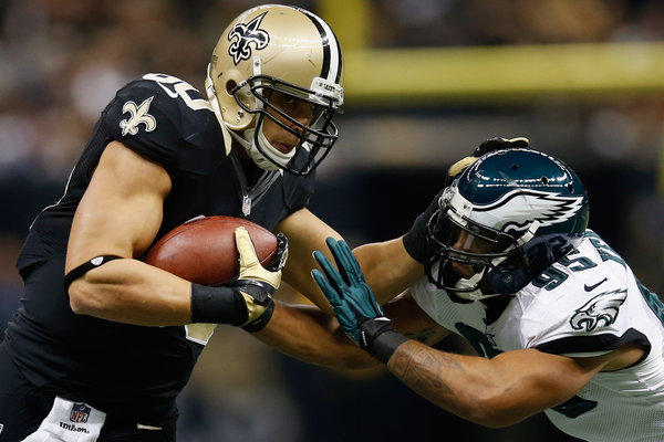 President Obama and Mitt Romney talked sports, not politics, during the halftime of Monday night's game between the New Orleans Saints and Philadelphia Eagles. Here the Saints' Jimmy Graham is pushed out of bounds by Mychal Kendricks of the Eagles.