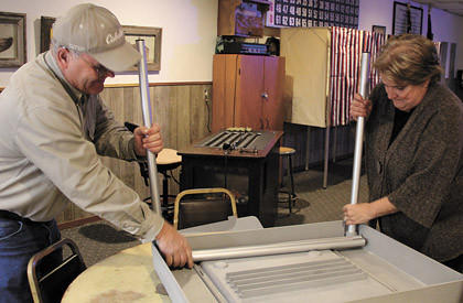 Day County employees Darrel Waddle, left, and Florine Gruby set up the special table Monday that will hold an AutoMark voting machine at the American Legion in Waubay. The site is one of eight in the county outside of Webster.
