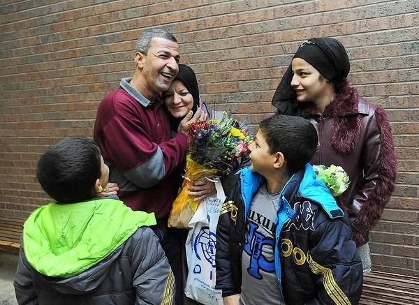 Abbas Hameed Khalaf of Northampton (left) embraces his wife, Lagga, while their children look on at Lehigh Valley International Airport last month.