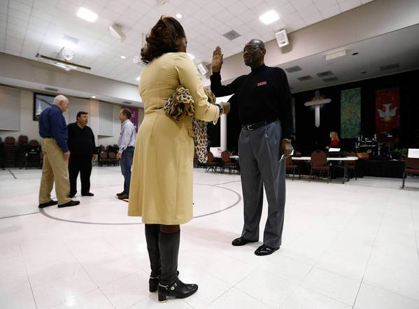 Poll worker Robin S. Davis, left,administers the Election Day Oath to Bill Partlow, chief judge for precinct 140, at Harrison United Methodist Church during the U.S. presidential election in Pineville, N.C.