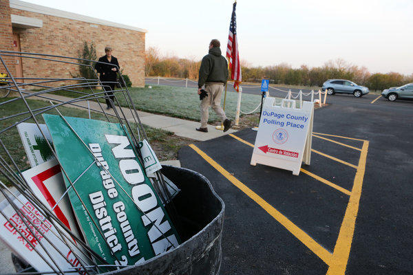 A trash can is filled with campaign signs outside the polling place at the American Legion Post 80 in Downers Grove in DuPage County.