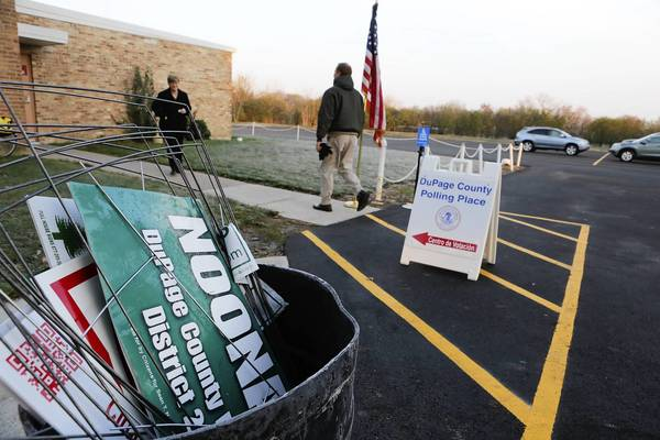 A trash can is filled with campaign signs outside the polling place at the American Legion Post 80 in Downers Grove.