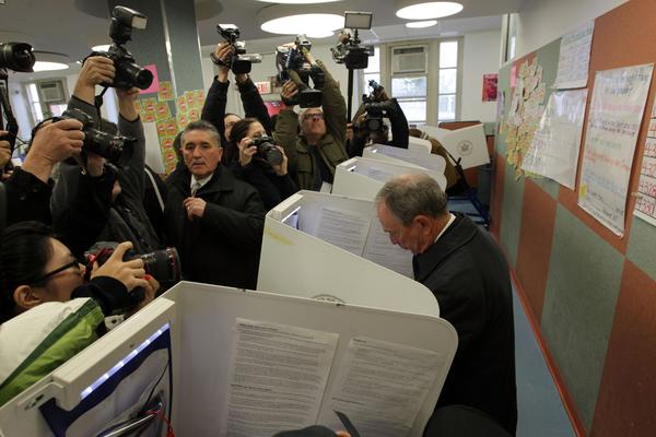 New York Mayor Michael Bloomberg, right, gets a lot of attention as he casts his ballot.