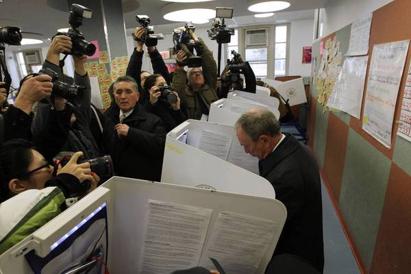 New York Mayor Michael Bloomberg, right, votes at his local polling station in New York. From a symbolic hamlet to a critical swing state neighboring the halls of power in Washington to the storm-scarred streets of metropolitan New York, Americans rose early to cast ballots for Barack Obama or Mitt Romney.