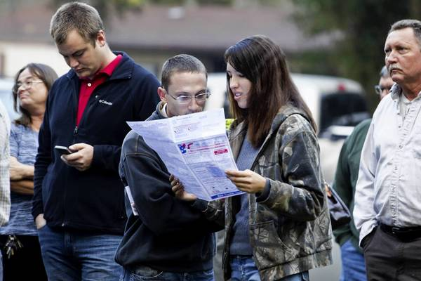 Robert Ceska (L) and Meagan Lewis look over a sample ballot just after dawn as people line up to vote at the County Polling House in Crawfordville, Florida. The swing state of Florida is a hotly contested battleground that offers 29 electoral votes. Recent polls show that the race between U.S. President Barack Obama and Republican presidential candidate Mitt Romney remains tight.