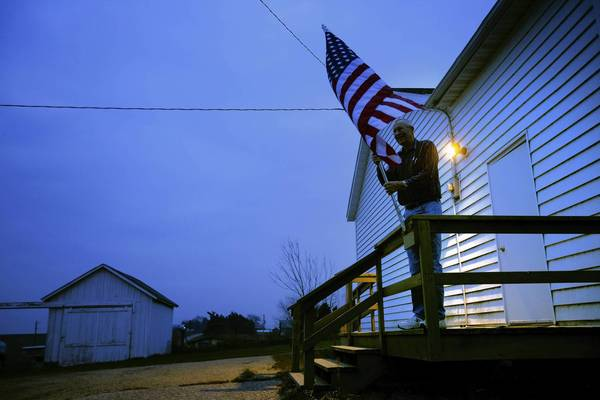 Election Inspector Jim Nodorft unfurls the American flag to hang it up outside the Smelser Town hall as the polls opened at 7 a.m. in Georgetown, Wisconsin.