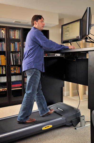 Dorry Segev, a transplant doctor at Johns Hopkins Hospital, does academic work at home on his computer while using a treadmill.
