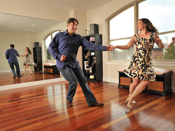 Dorry Segev, left, and Sommer Gentry, practice swing dancing in their dance studio. Their four-level Canton rowhouse is a haven for their varied interests in music, dancing, and entertaining, as well as their academic research.