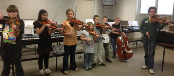 Andy Tuck (right) of Charlevoix, a senior at the University of Michigan majoring in music performance, visits with Boyne Falls strings students, (from left) Ben Wheeler, Alicia Whennen, Jordin Gellis, Kristina Rackow, C.J. Cousineau, Walter Tieber and Clint Covell. Tuck was a recent guest soloist with the Great Lakes Chamber Orchestra.