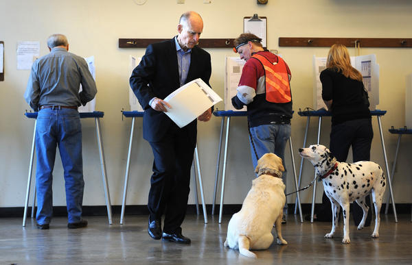 California Gov. Jerry Brown goes to turn in his completed ballot at Fire Station 6 in Oakland.