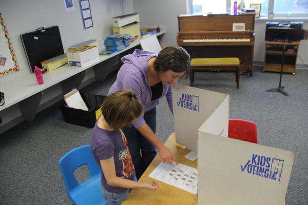 Second-grade teacher Megan Barnett helps student Lauren Dosch fill out her Kids Voting ballot.