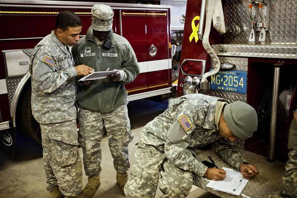 Members of the Army National Guard fill out absentee voter ballots for the presidential election while temporarily stationed along the New Jersey coastline helping with Superstorm Sandy cleanup in Bay Head, N.J.