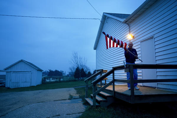 Election Inspector Jim Nodorft unfurls the American flag to hang it outside the Smelser Town hall before polls open at 7 a.m. in Georgetown, Wis.