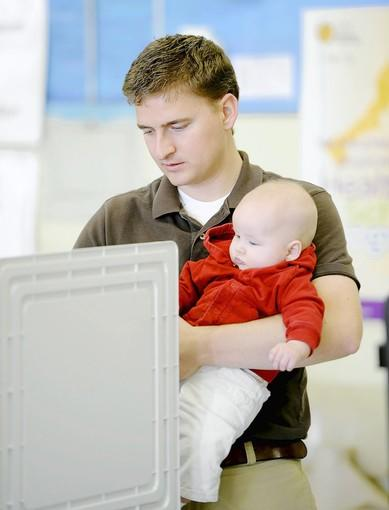 Justin Wilson ,of Roland Park, holds his 4-month-old daughter, Elise, while voting at Roland Park Elementary/Middle School Nov. 6.