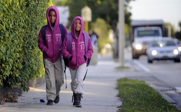 Two young girls bundle up for their walk to school in Fort Lauderdale.
