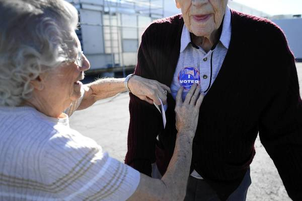 "Pauline Vallee, left, helps Robert Krack with his ""I Voted"" sticker after voting at the polling station at John Fremont Middle School in Las Vegas. Krack, 91, has voted in every presidential election since Franklin D. Roosevelt."
